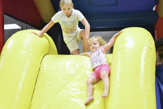 Roslyn Chambers, left, 9, daughter of Amber and Derek Chambers, watches as her cousin Charlee Marcus, 1, both of Sidney, daughter of Cala and Adam Marcus, goes down a slide during the Northtowne Church of God's Annual Kid's Carnival Wednesday, Aug. 15. Free food, face painting and flavored ice were some of the things offered at the event which was moved indoors due to rain.