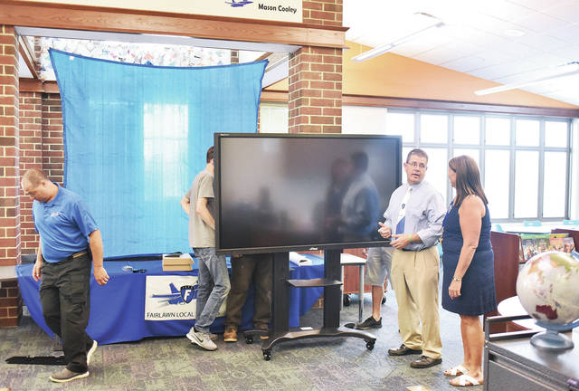Fairlawn Elementary Principal Karen McRill, far right, of Anna, talks with Fairlawn High School Principal John Stekli, second from right, of London, while a new interactive screen is unveiled before the start of a ceremony celebrating Fairlawn's new media room. The media room is the school's newly outfitted library. Five book cases were removed making room for nesting tables that are designed to be quickly stored away making an open space for other activities. The new additions will allow a Workforce development class to be held in the room. Helping set up the new screen is Fairlawn maintenance supervisor Dank Worth, far left, of Troy.