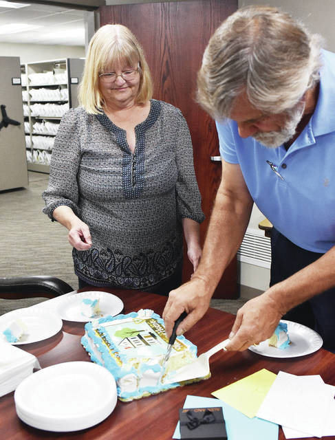 Deb Gibbs, left, watches her husband Chris Gibbs both of Maplewood, cut her retirement cake on the last day of her job at the Shelby County Auditor's Office, Wednesday, Aug. 15, where she has worked for the last 37 years. Gibbs started her job when Thelma White was the auditor. Gibbs surprised his wife with the cake and a group of close friends and relatives.