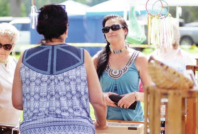 Lisa Porter, left, of Thornsville, sells earings to Deanna Totten, of New Albany, at the seventh annual Honoring Our Veterans and First Responders Pow Wow Saturday, Aug. 18 at the Shelby County Fairgrounds.