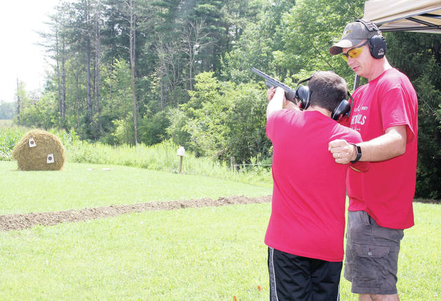 Jason Barhorst, of Minster, helps Cody Chapman, 13, of Waynesfileld, son of mike and Jessica Chapman, shoot a 20 gauge shotgun at the Shelby County Whitetails Unlimited Saturday, Aug. 18.