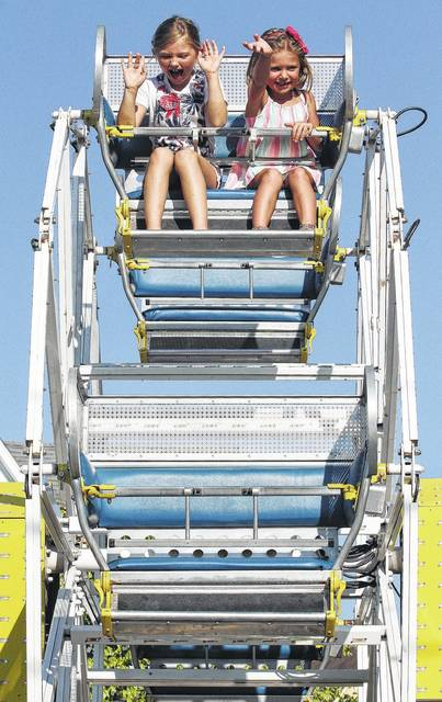 Morgan Sommer, left, of Minster, daughter of Jeff Sommer, screams as Ava Meier, of Maria Stein, waves to her mom, Jenny Sommer, while riding a kids ferris wheel at the 2017 Bremenfest. Ava is also the daughter of Greg Meier.