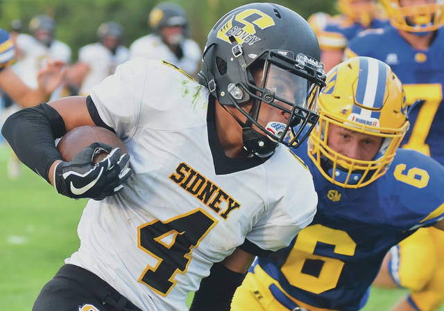 Sidney's Darren Taborn runs the ball as St. Marys' Christian Triplett follows during a season opener on Friday at Skip Baughman Field in St. Marys.