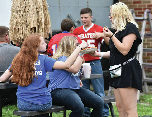 Amber Waters, left, 13, daughter of Kim Water, grabs a piece of Jayden Ferryman's, 13, both of DeGraff, daughter of Jennifer and Todd Allen, blooming onion at the DeGraff Country Fair Saturday, Aug. 25.