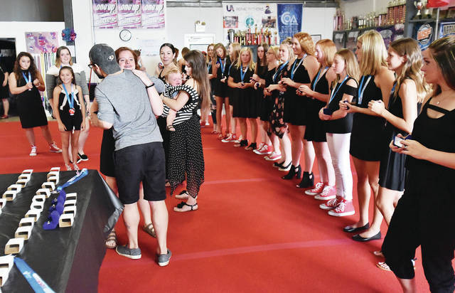 Ashley Schuh, 14, of Wapakoneta, gets a hug from her coach Ty Batty, of Ann Arbor, Mich., as she accepts her ring during a team ring presentation ceremony at the United Tumbling Academy Sunday, Aug. 26.