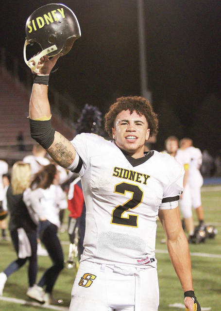 Sidney running back Isaiah Bowser hoists the Battered Helmet toward Sidney fans following a 34-33 win over Piqua on Sept. 29, 2017 at Alexander Stadium. Bowser was a Mr. Football finalist after amassing 3,192 all-purpose yards and scoring 32 touchdowns last year.