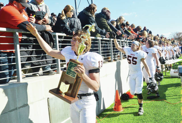 Minster's Jacob Hoying, front, holds the Division VII state championship trophy as he high-fives fans following the team's 32-7 win over Cuyahoga Heights at Tom Benson Hall of Fame Stadium in Canton on Friday, Dec. 1, 2017. Minster suffered a four-game losing streak in regular season for the second consecutive year but finished the year on an eight-game winning streak.