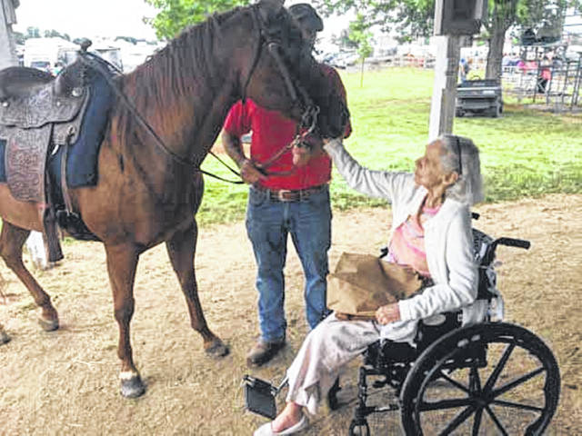 Georgi Moser, of New Bremen, gets up close and personal with a horse during Senior Day at the Auglaize County Fair. Moser was with a group of residents of Elmwood Assisted Living.