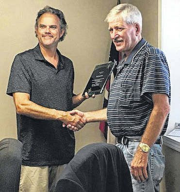 Botkins Village Mayor Steve Woodruff presents a plaque of appreciation to retired firefighter Ed Burden at the village council meeting, Tuesday, Aug. 14, in honor of his 40 years of service with the Botkins Fire Department.