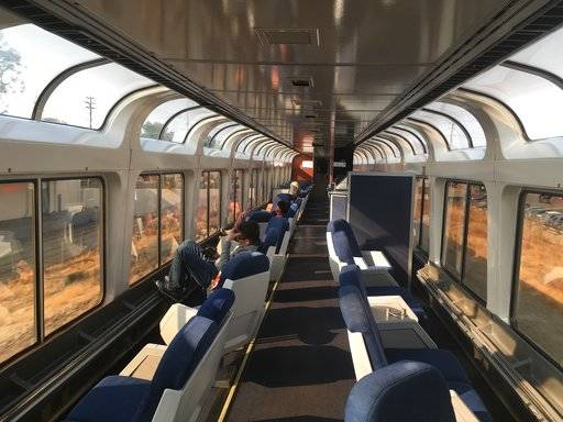This Dec. 16, 2017 photo shows passengers lounging in the observation car of Amtrak's Coast Starlight on the way from Los Angeles to Seattle. The scenic 35-hour route travels from southern California to Seattle. (AP Photo/Nicole Evatt)