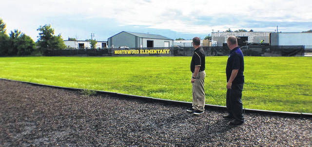 Northwood Elementary School Principal Eric Barr, left, and Jeff Pollard, owner of Sidney Tire, look at the new sign Pollard had installed on the fence between the two properties.
