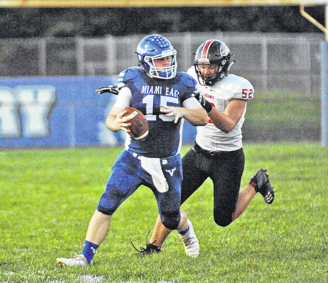 Miami East's quarterback Ian Gengler is tracked down by a Fort Loramie defender during a Cross County Conference game on Friday in Casstown.