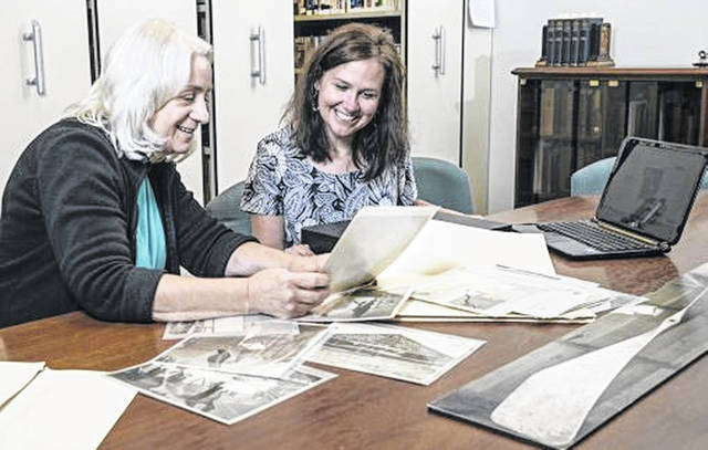 Dawne Dewey, head of Wright State's Special Collections and Archives, left, and archivist Toni Vanden Bos examine photos from the Wright Brothers Collection in the Special Collections and Archives in Dunbar Library.