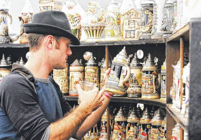 Josh Robinett, of Columbus, gets a closer look at a beer stein at 2017 Minster Oktoberfest.