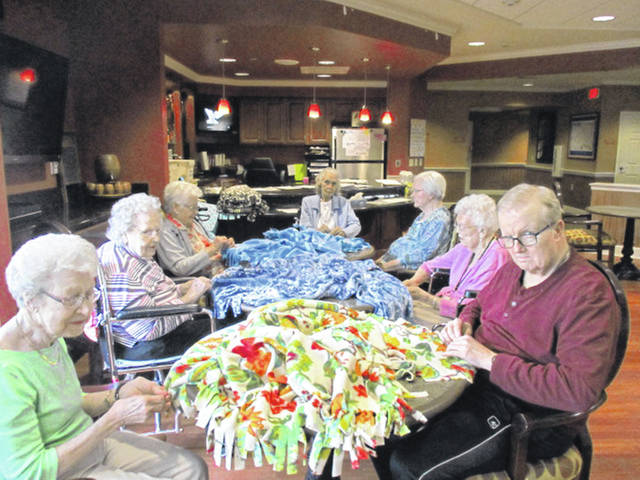 Residents of Elmwood Assisted Living in New Bremen tie knots in blankets for Blanketeers, a volunteer organization, based in New Bremen, that makes coverlets for cancer patients. Emilie Britton, of Blanketeers, visits the facility monthly to lead the craft activity.