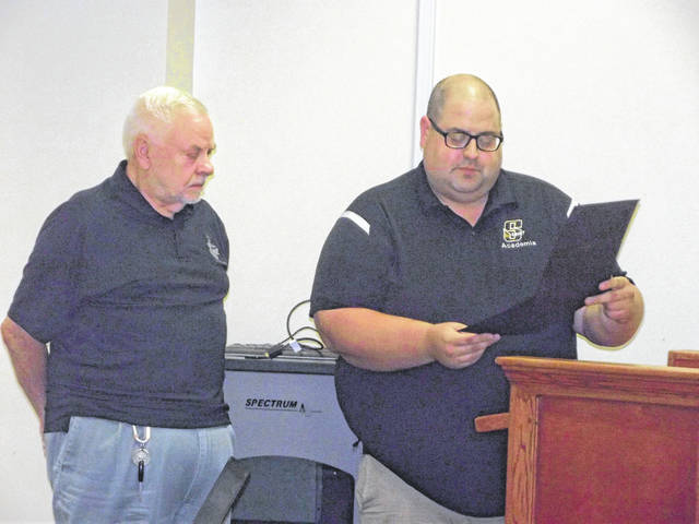 Sidney High School social studies teacher Brett Bickel, right, reads a proclamation honoring Chuck Craynon, American Legion Post 217 Americanism chairman, for his dedication to the program at Sidney High School. Craynon is stepping down after serving for 16 years as chairman.