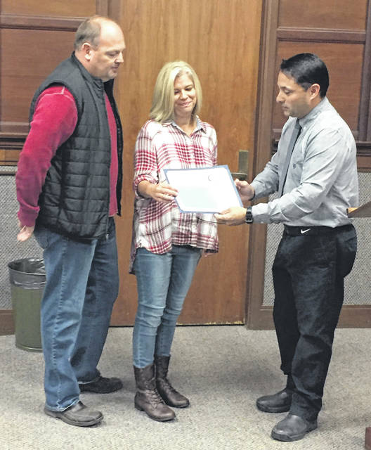 Homeowners Tony and Elaine Kerns, left, of 1048 E. Hoewisher Road, are presented with Sidney's 2018 Neighborhood Beautification Award by Sidney Code Enforcement Officer James Vagnone during Sidney City Council's meeting Monday evening.