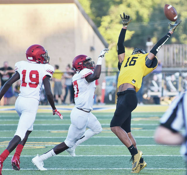 Sidney junior wide receiver Lathan Jones goes up for a pass with pressure from Trotwood defenders during a Greater Western Ohio Conference crossover game at Sidney Memorial Stadium on Friday. Jones is second on the team in receptions (10) and receiving yards (141) this season.