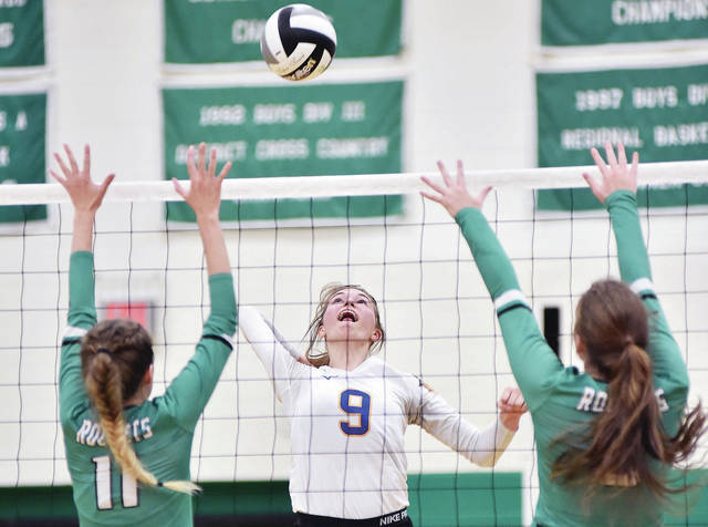Russia's Samantha Gaerke spikes as Anna's Macy Wiktorowski and Madison Roe defends during a Shelby County Athletic League match on Tuesday in Anna.