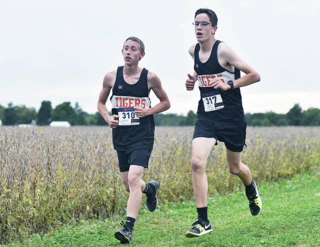 Jackson Center's Elisha Burch, left, and Grant Lowry, run in a cross country meet on Thursday at Fairlawn.