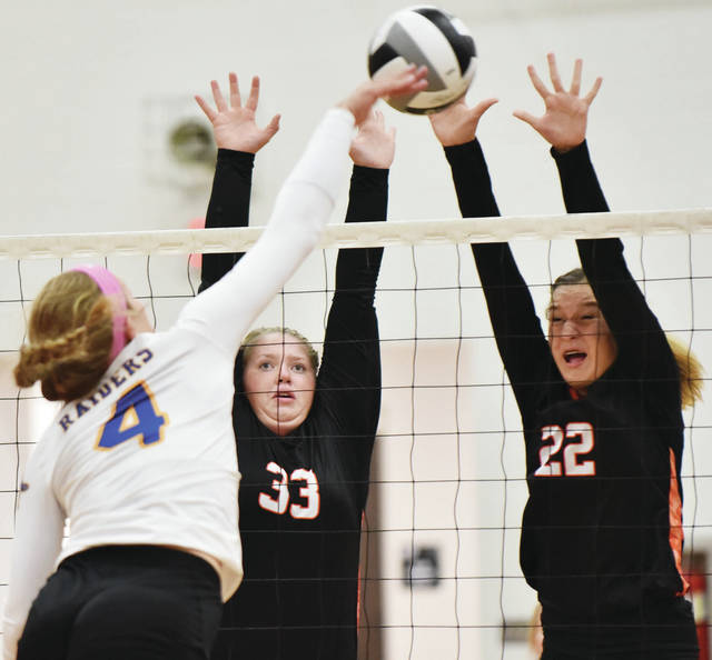 Russia's Laurissa Poling spikes towards Jackson Center's Katie Clark and Deja Wells at Jackson Center Tuesday.