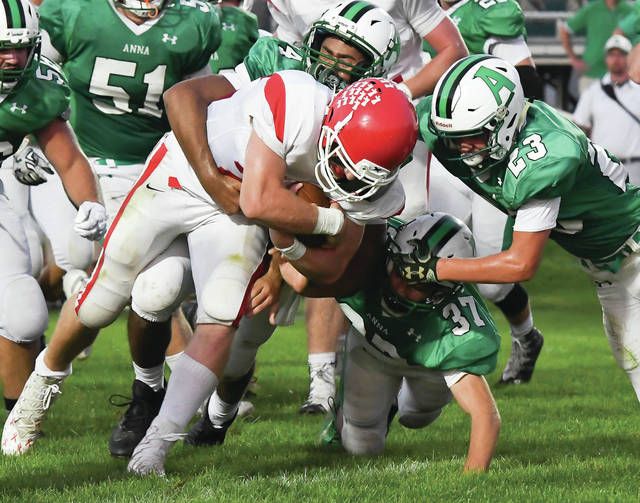 From left to right, Anna's Kam Steward, Brandon Shannon, and Isaac Lininger pull down St. Henry's Zach Niekamp during a two-point conversion attempt in overtime of a Midwest Athletic Conference game last Friday in Anna. The stop allowed the Rockets to hold onto a 28-27 win.