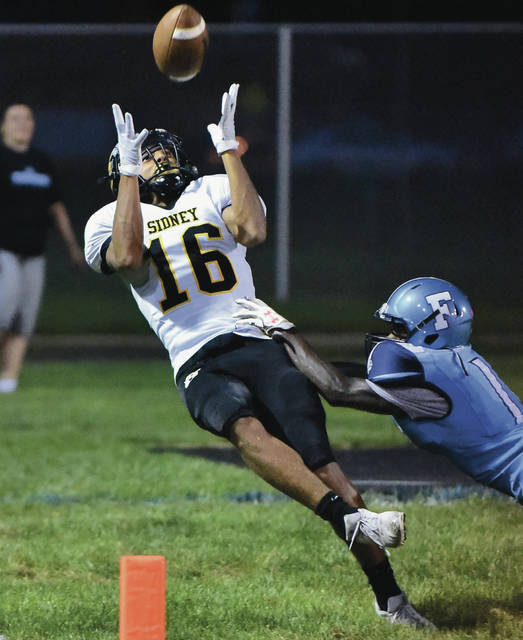 Sidney's Lathan Jones hauls in a pass in the end zone while covered by Fairborn's Richard Peterson during a Greater Western Ohio Conference crossover game on Friday in Fairborn. Jones was ruled out-of-bounds on the play, but the Yellow Jackets scored a short time later.