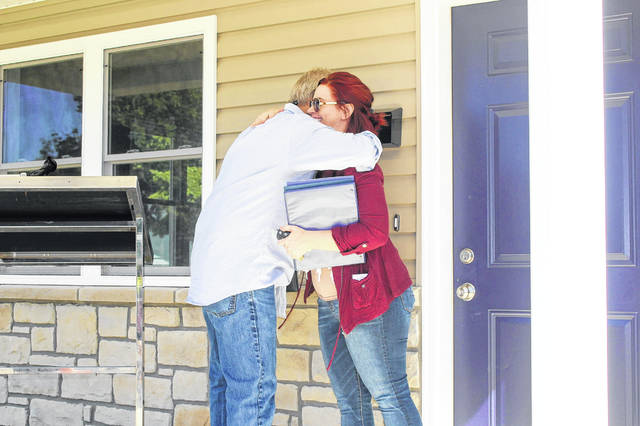 Paul Hoying, owner of Hoying and Hoying Builders and construction manager for the Habitat for Humanity of Miami and Shelby Counties project, gives Kelly Beemer a hug after he presented her the keys to her new home Sunday afternoon.