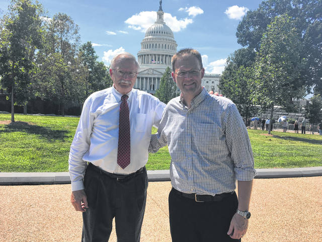 Sidney Mayor Mike Barhorst and his son, Ursuline Academy Principal Tom Barhorst, pose for a photo while waiting in line outside the United States Capitol to attend the viewing for the late Senator John Sidney McCain.