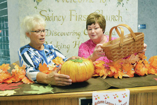 Co-chairwomen Barri Grandey, left, of Sidney, and Kathy Husemann, of Maplewood, organize decorations for the annual Autumn Leaves Luncheon, recently. The luncheon is scheduled for Oct. 2 at the First United Methodist Church.