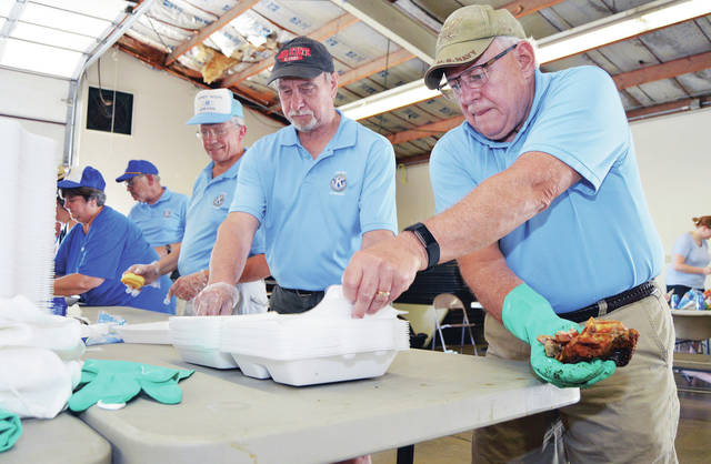 Putting together chicken dinners are, left to right, Nancy Deafenbaugh, and Merrill Asher both of Sidney, Gary Carter, of rural Fort Loramie, and past Kiwanis presidents Phil Warnecke and Rick Lunsford, both of Sidney. The Kiwanis members were holding their annual Sidney Kiwanis annual Labor Day BBQ chicken sale at the Shelby County Fairgrounds Monday, Sept. 3.