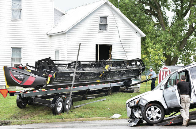 A piece of farm equipment being pulled by a truck swung into a house at the intersection of county Road 25a and state Route 274 near Botkins shortly before 5 p.m., Thursday, Sept. 6. The vehicle, right, being towed away was clipped in the accident. A pregnant woman driving the vehicle was taken to the hospital for evaluation. A preliminary investigation suggests the truck hauling the farm equipment may have swerved to avoid a semi that was hauling produce at the intersection. Only the drivers of all three vehicles were involved in the accident. No one in the house was injured.
