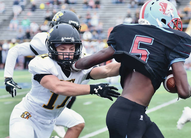 Sidney senior defensive back Caleb Harris tries to tackle Belmont's Brian McKenzie during a nonconference game last Friday at Welcome Stadium in Dayton. The Yellow Jackets will host Trotwood-Madison in a Greater Western Ohio Conference crossover game on Friday.