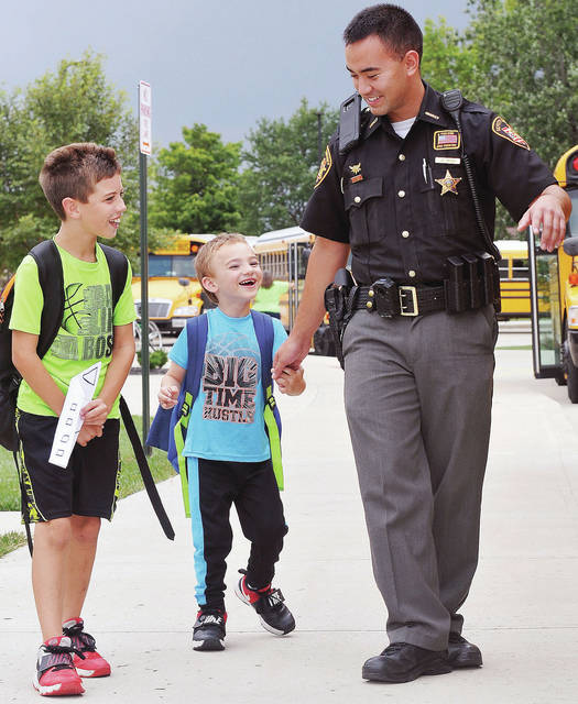 Preston Armstrong, 10, left, and his brother, Dalton Armstrong, 6, both of St. Marys, are walked out to their waiting bus after school in Botkins by Shelby County Sheriff's Deputy Josh Spicer, recently. The boys are sons of Heather and Scott Armstrong.