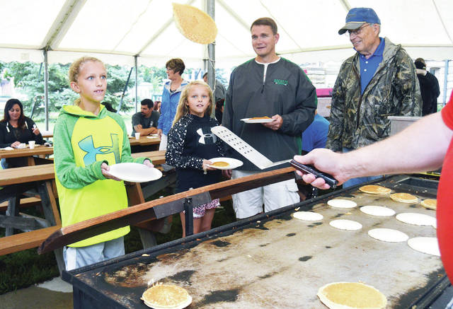 Dana Pleiman, 11, left to right, waits to catch a pancake, as her sister, Eva Pleiman, 9, and their father, Jeff Pleiman, all of Anna, and Roger Mowery, of Sidney, watch. Flipping the pancake is Matt Block, of Lewis Center, of Chris Cakes. The Sidney Rotary Club's pancake breakfast was on the courtsquare, Saturday, Sept. 9. Sausage and apples were also served. The girls are also the children of Jenny Pleiman.