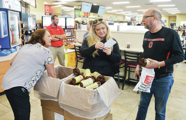 Attending the grand opening of Speedway, along Michigan St. in Sidney, Saturday, Sept. 8, are, left to right, staff members Stephanie Roginski, of Millbury, and Ryley Wood, of Findlay, and customer Roger Barhorst, of Troy.