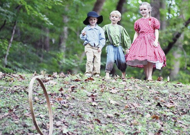 Rolling a hoop down a hill for fun are, left to right, Sam Ling, 4, of Ashland, son of Becky and Bobby Ling, Hayden Rogers, 6, his sister Natalie Rogers, 9, both of Wellington, children of Melissa and Steven Rogers. The trio were dressed as children of Union soldiers at Tawawa Park Saturday, Sept. 15.