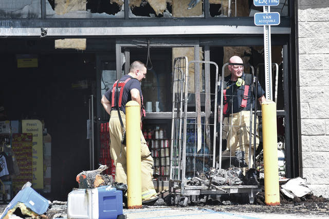 Sidney firefighters investigate a fire which started by a clothes rack outside the Dollar General on Russell Road and spread to the building around mid day Sunday, Sept. 16.