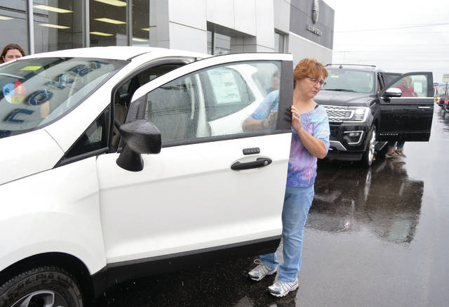 Jeannine Jordan, of Lima, gets into a spiffy new vehicle for a free joy ride at Buckeye Ford in Sidney, recently. Jordan was one of many people who took advantage of the school fundraising event, Drive 4 UR School. Botkins and Fairlawn benefited each time someone test drove a new car.