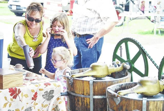 Sue Baber, left, puts some chocolate syrup on her granddaughter Ava Baber's, right, both of Wapakoneta, daughter of Adam Baber and Sara Zink, old style ice cream. Watching them is Emma Donovan, center, of Wapakoneta, daughter of Bobbi and Scott Donovan. The ice cream was being sold by Grandma Moses' Homemade Ice-Cream at the 2017 Lake Loramie State park Fall Harvest Festival.
