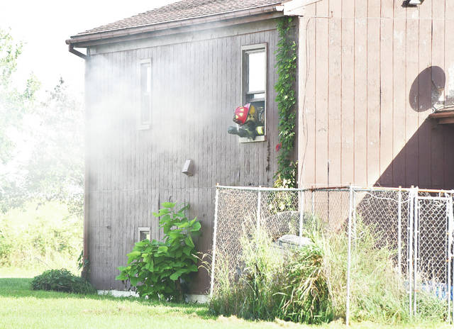 A Jackson Center firefighter looks out a smoke-filled window in a house on fire at 13490 Pasco-Montra Road east of Anna around 5 p.m., Thursday, Sept. 20. Firefighters from Anna, Botkins and Van Buren Township also responded. The Shelby County Sheriff's Office directed traffic. The fire was quickly brought under control.