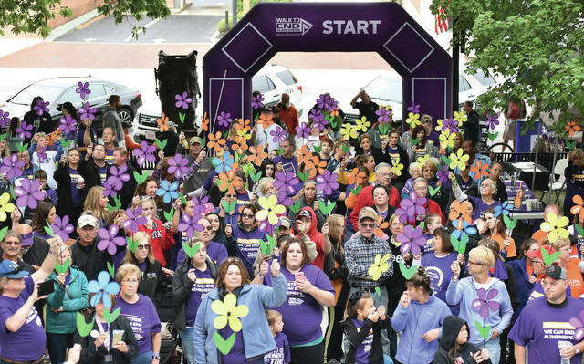 People raise their Alzheimer's flowers during a ceremony before the start to the Walk to End Alzheimer's starting on the courtsquare Saturday, Sept. 22.
