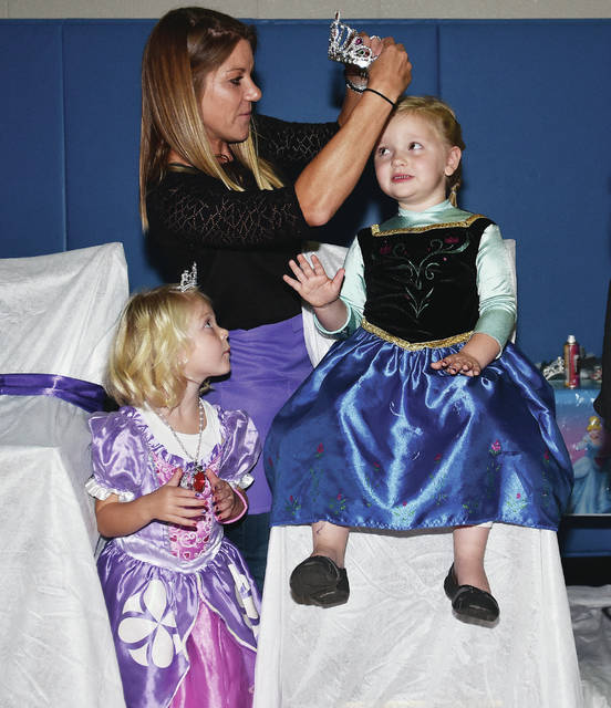 Chloe Dunham, left to right, 4, watches her mom, Joni Dunham, both of Sidney, put a crown on McKinley Groves, 4, all of Sidney, daughter of Phil and Erin Groves, after working on her during the fifth annual Princess Spa Day Sunday, Sept. 30. Chloe is also the daughter of Brad Dunham.