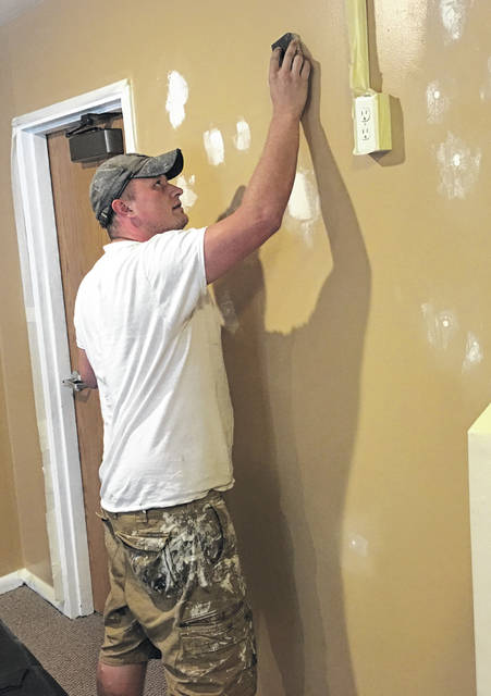 Shane Lambert, owner of the newly established business, LP&P Powerwashing and Painting, sands down patches on a drywall he is about to paint at Cornerstone Assembly of God, in Sidney, earlier this month.
