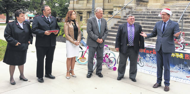 Announcing Mark's Toys for Tots Bike Drive are, left to right, Capt. Chastity Hansen and Capt. Joseph Hansen with The Salvation Army of Shelby County, Shelby County Commissioners Julie Ehemann, Tony Bornhorst and Bob Guillozet, and Mark Reedy, of Piqua. Reedy runs the bike program and made the announcement on the Shelby County Courthouse steps Thursday, Sept. 27.