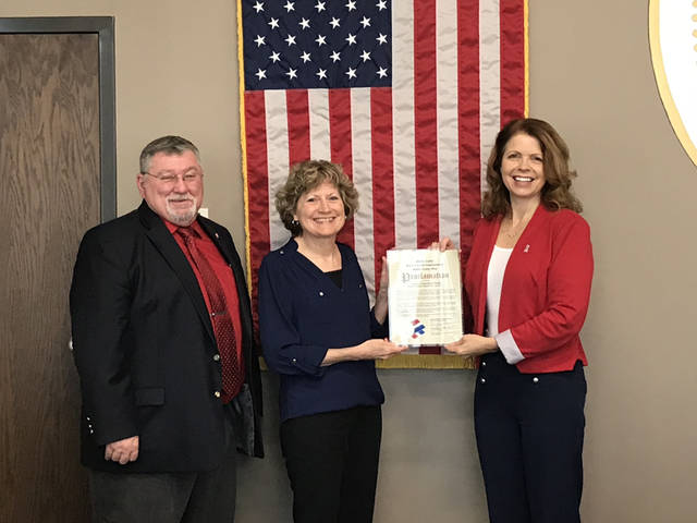 Shelby County Commissioners Bob Guillozet, left, and Julie Ehemann, right, present a proclamation of the National Day of Action to Cheri Drinkwine, director of Shelby County Homeland Security and Emergency Management, Tuesday, Sept. 11, in Sidney.