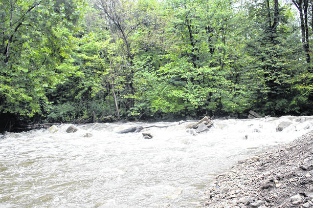 Water rushes through Tawawa Park, in Sidney, near Meyer Meadow, Monday. The torrent receded during the week.