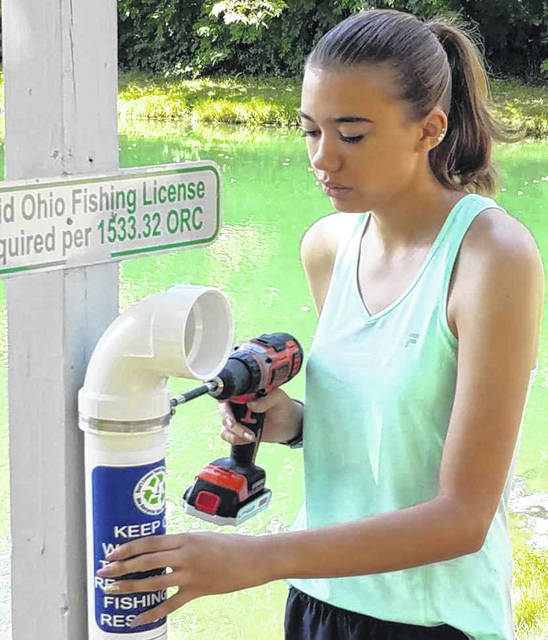 Sam Newman, 21, of Sidney, installs a fishing line receptacle near the river in Sidney. She has installed three so far; two at Roadside Park and one at Tawawa Park. She plans to install two more at Tawawa.