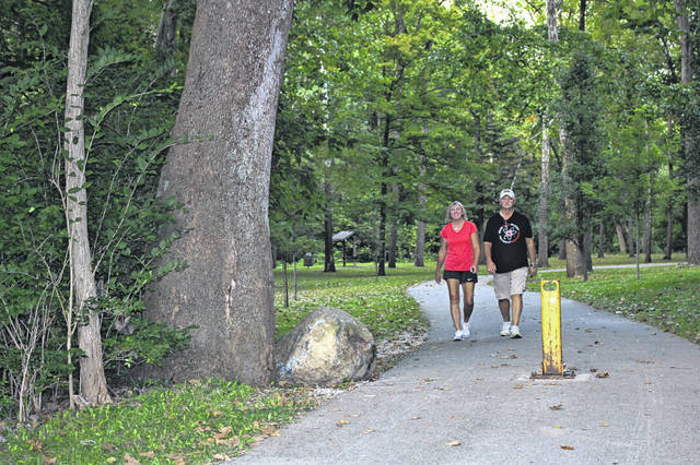 Peggy and DJ Baird, of Sidney, take a relaxing stroll through Tawawa Park Monday night. They were enjoying the weather and sunset during their stroll.