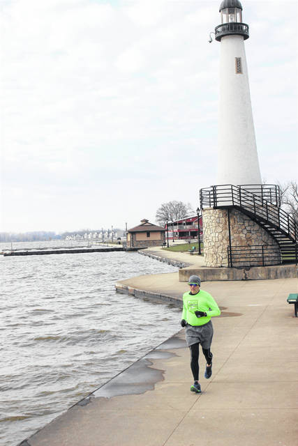 Rod Carpenter trains for his marathons by running by the lighthouse in Celina on Grand Lake.